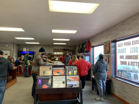 Customers browse the selection of records, and wait to make their purchases,  at the store