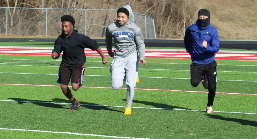 Members of the football team sprint down the field during practice at Alton public school stadium.